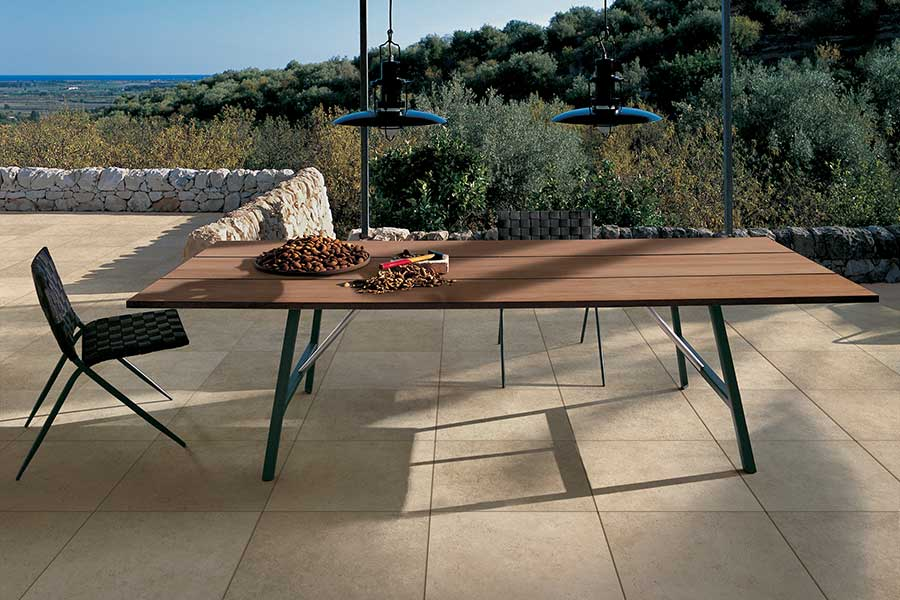 Outdoor porcelain tiles in summer patio with furniture