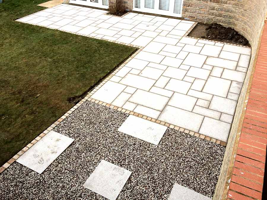 Granite paving slabs in light cinder colour laid in a random pattern with a retaining boarder of single granite setts in ember colour