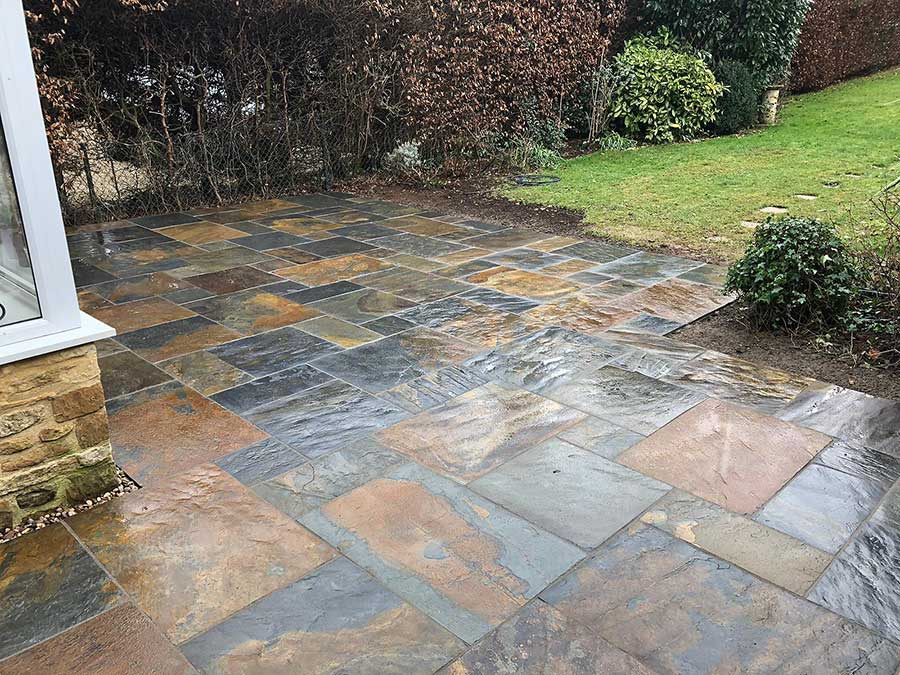 A rear patio featuring natural slate paving slabs in rusty colour