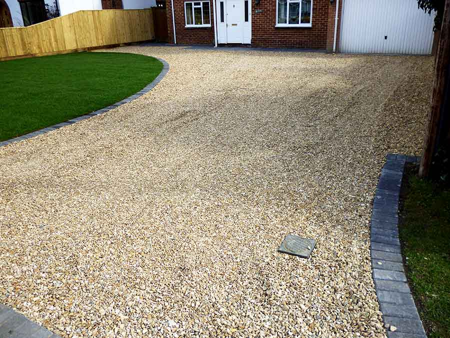 A new enlarged gravel driveway featuring 20mm Golden Flint shingle created by AWBS Landscaping at a family home in Abingdon