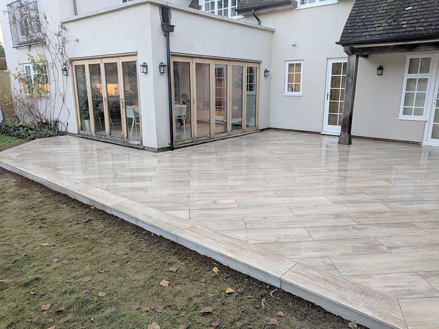 The AWBS Landscaping team removed a rotten timber deck from the rear of this large house in Abingdon and replaced it with 64 m2 of smart new wood effect exterior porcelain paving